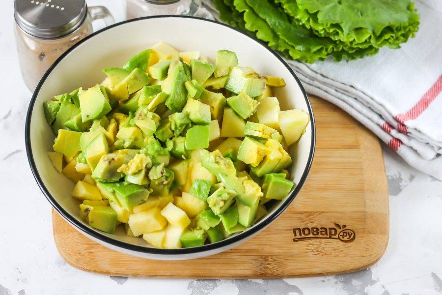 Промойте авокадо, счистите кожуру, разрежьте плод пополам, и удалите косточку. Нарежьте мякоть кубиками и добавьте в емкость.