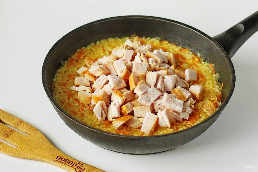 Когда рис будет почти готов добавьте нарезанное куриное филе (у меня грудка). Под крышкой, на небольшом огне доведите блюдо до полной готовности. Затем снимите сковороду с огня и дайте настояться рису еще 10-15 минут.