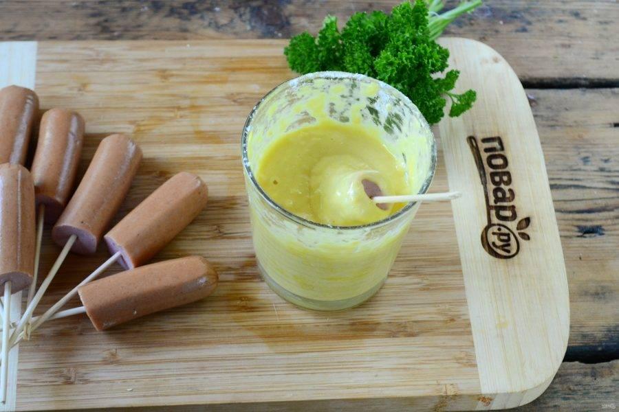 Обмакните сосиски в подготовленный кляр, чтобы он полностью покрывал сосиску.