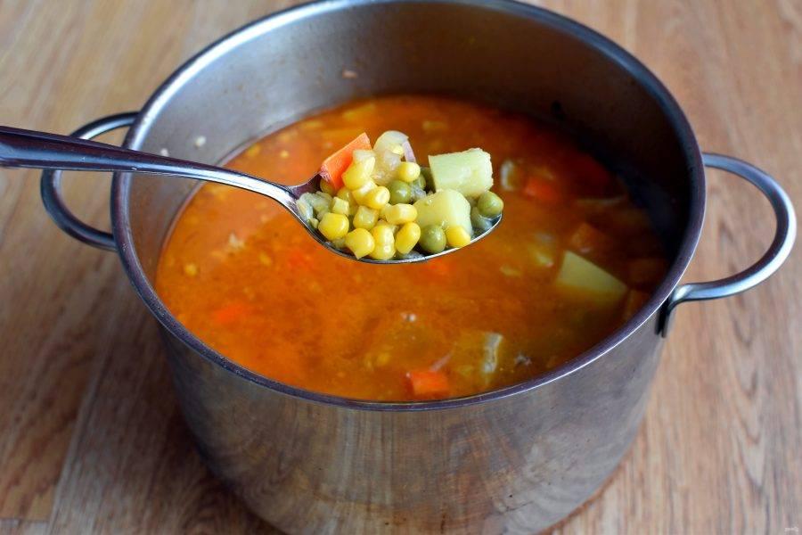 Влейте горячий бульон, чтобы он покрыл содержимое кастрюли на два пальца. Это густой суп. Тушите на небольшом огне почти до готовности картофеля.     Если у вас кукуруза и горошек замороженные, добавляйте их в суп сразу после закипания картофеля. Если же консервированные, то добавляйте в конце.