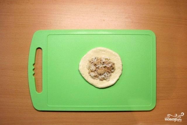 13.Готовое тесто разделяем на кусочки, каждый из которых раскатываем или разминаем, формируя при этом круг. В центр кладем начинку.