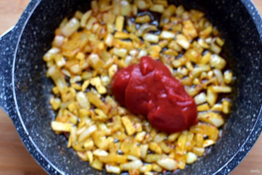 Добавьте к луку томатную пасту и все прогрейте.