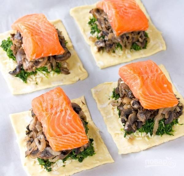 3.Раскатайте два листа слоеного теста в тонкий пласт, затем разрежьте оба на небольшие квадратики. По центру половины из них выложите отварной рис, затем — слой зелени и грибы, поверх уложите кусочек рыбы. Накройте каждый кусочек теста с начинкой другим кусочком теста, а края прижмите вилкой, смажьте каждый пирожок взбитым яйцом.