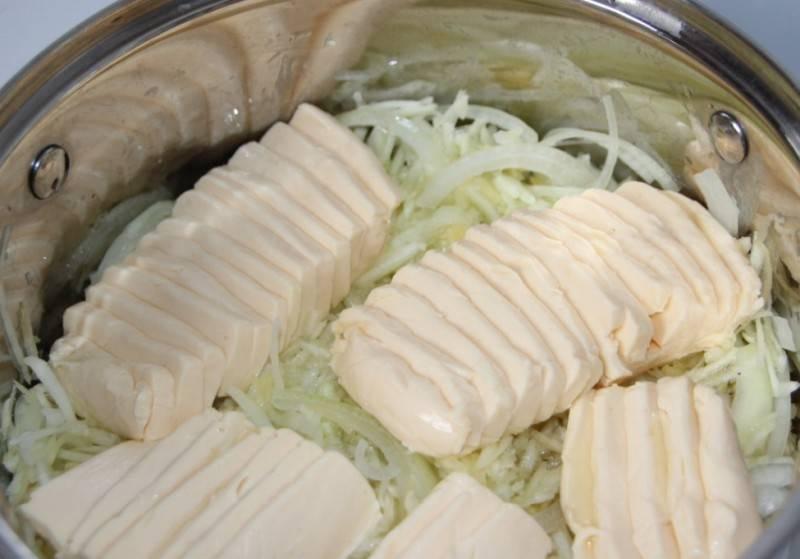 Далее мы отжимаем тертые кабачки от сока и перекладываем их в кастрюлю, добавляем оливковое масло, репчатый лук и плавленый сыр, ставим кастрюлю на медленный огонь.