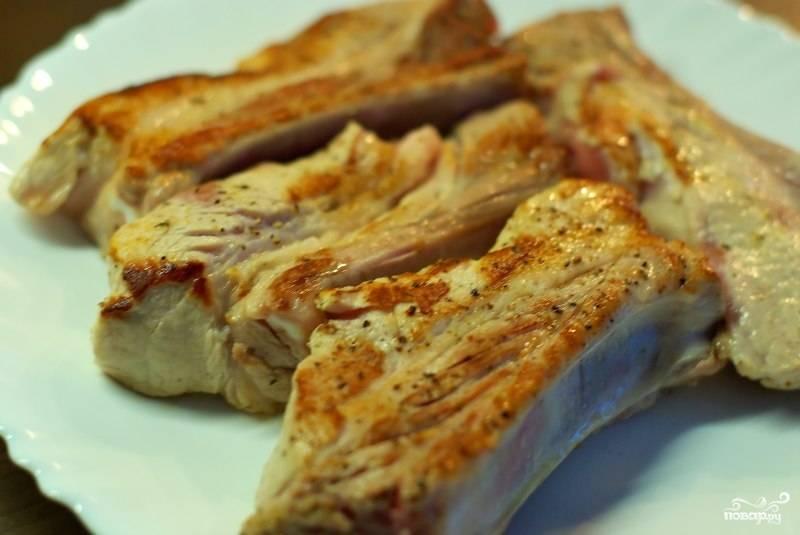 Обжаренные ребрышки выкладываем на тарелочку, а сами в это время в той же кастрюльке обжариваем мелко нарезанный лук и чеснок.