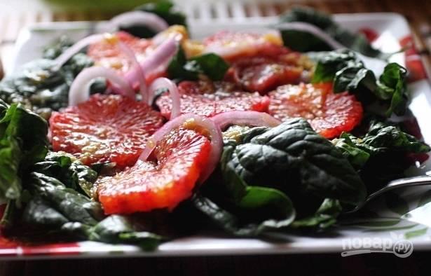 6. На тарелку для подачи выложите вымытый и обсушенный шпинат. Добавьте лук и апельсины. Полейте все заправкой — и салатик можно подавать.  Приятного аппетита!