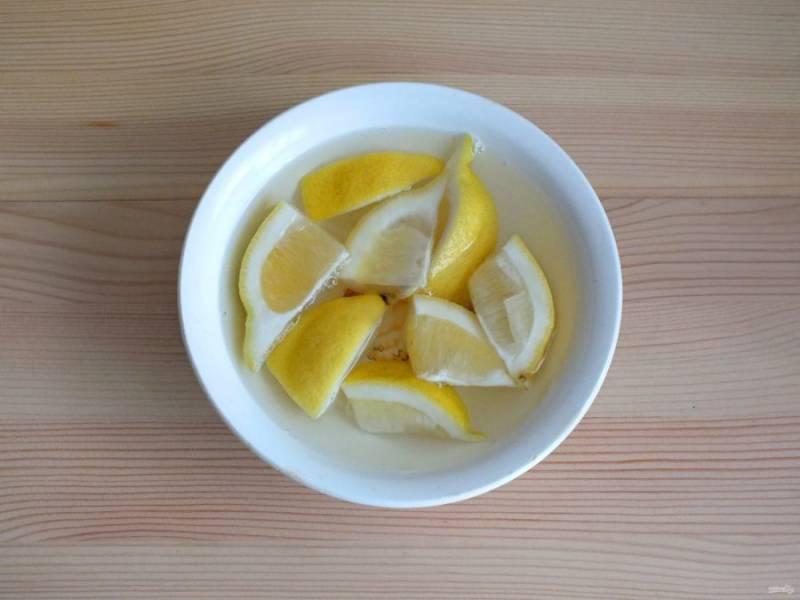 Приготовьте пропитку. Половинку лимона разрежьте на кусочки. Залейте кипятком и оставьте на 15 минут, для того чтобы вышла горечь.