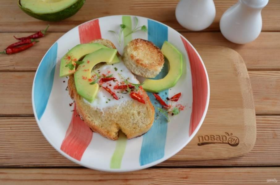 Авокадо вымойте, разрежьте на половинки и снимите кожуру. Порежьте ломтиками. На тарелочку положите тост с яйцом, украсьте ломтиками авокадо, соль-перец добавьте по вкусу, зелень и к столу! Подавайте тосты с любимыми острыми соусами!