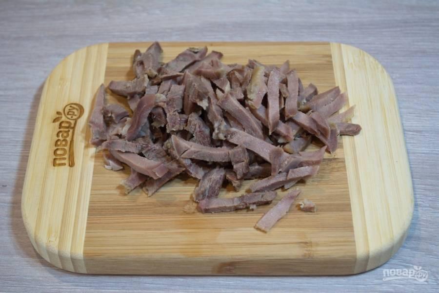Для приготовления салата с языком и шампиньонами нам необходимо взять отварной язык. Язык нарежьте небольшими полосочками.