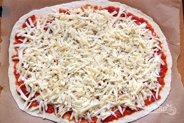 3. Выложите на тесто томатный соус и распределите его по всему тесту, оставьте по 1,5 сантиметра от края. Поверх соуса выложите сыр и добавьте черный молотый перец.