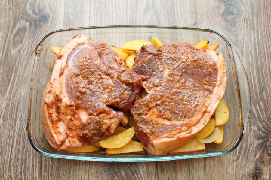 Достаньте форму с картофелем и выложите сверху мясо на косточке.