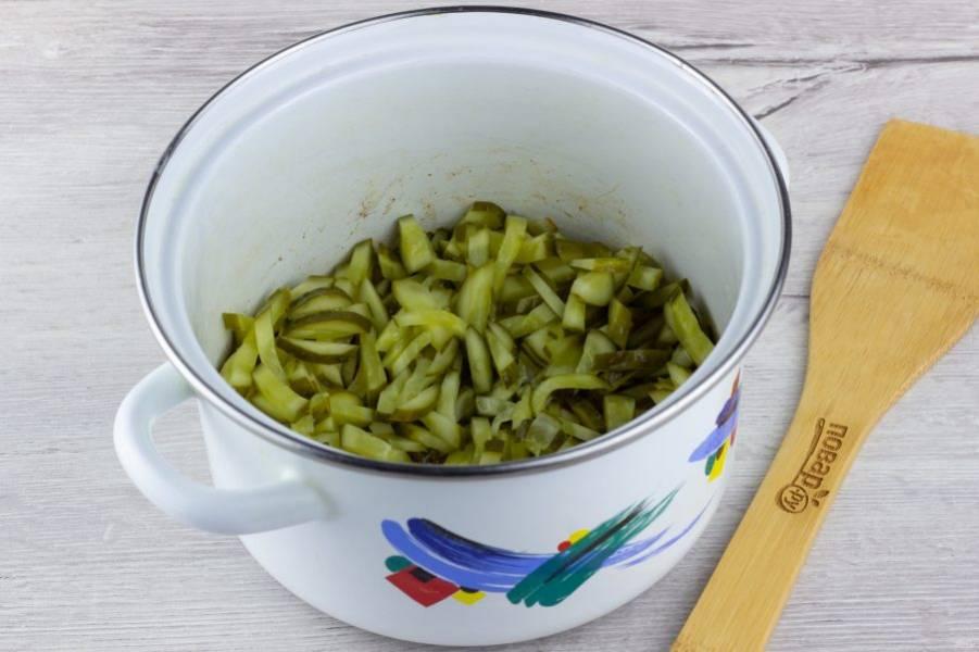 Огурцы нарежьте мелкой соломкой и добавьте к обжарке. Тушите ещё 3-4 минуты.