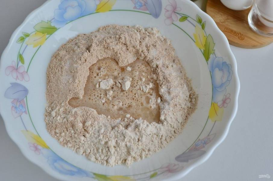 Влейте воду с дрожжами и замесите тесто. Тесто лучше всего замешивать комбайном или миксером (не менее 10 минут). Оно плотное и тугое.