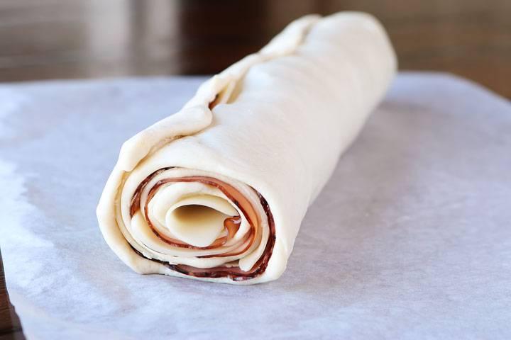 3. Сворачиваем лаваш в рулет. Нарезаем его, как колбасу, средними кусочками. Выкладываем их в форму для запекания.