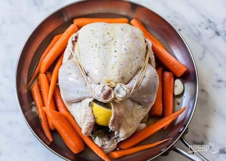 5.Выложите куриную тушку на блюдо, очистите морковь и нарежьте ее тонкими ломтиками, затем выложите вокруг курицы. Влейте вокруг куриный бульон, а курицу смажьте растительным маслом.