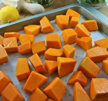 2. Выложите тыкву на противень. Сбрызните оливковым маслом, добавьте щепотку соли и перца. Лучше использовать белый перец, чтобы не портить яркий цвет овоща. Отправьте в разогретую духовку, и запекайте 25-30 минут, в зависимости от размера кусочков.