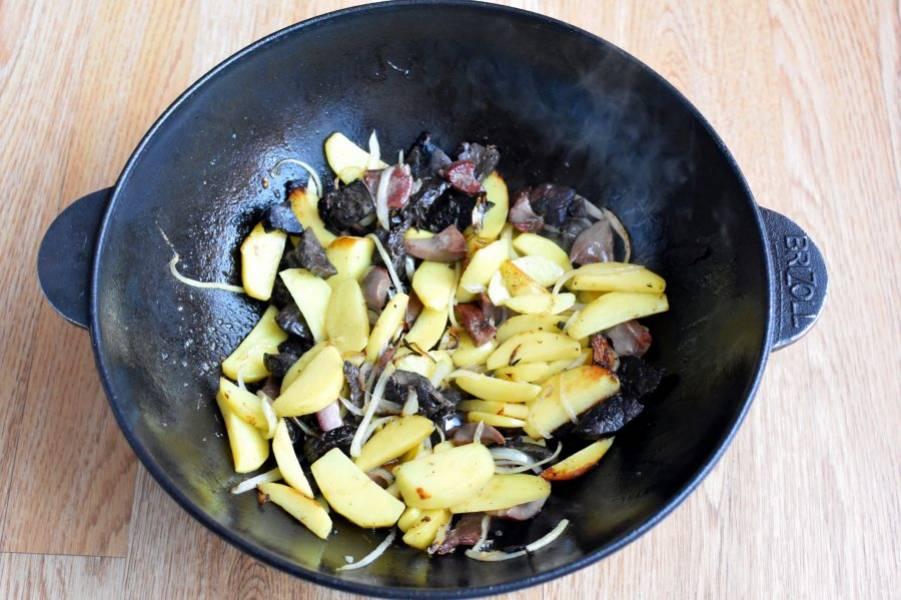 Выложите лук, дайте ему немного подрумяниться. Добавьте картофель не толстыми дольками. Жарьте, помешивая, до легкой корочки на картофеле.