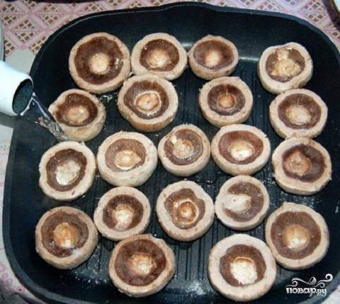 2.Противень смазать маслом и выложить на него  шляпки грибов. На дно противня налить немного горячей воды. Разогреть духовку до 200 градусов и запекать грибы 10 минут.