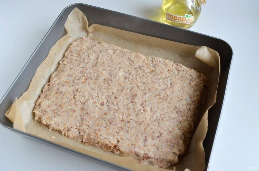 5. Смажьте пергамент растительным маслом. Утрамбуйте плотно кашу слоем в 1,5 см. Разровняйте ложкой или лопаткой. Поставьте в разогретую духовку (120–130 °С) на 10 минут. Остудите.