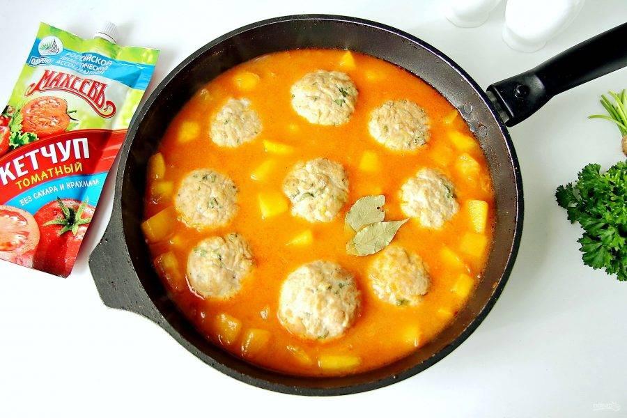 Добавьте лавровый лист, можно добавить перец горошком и опустите в соус запеченные тефтели. Накройте крышкой и тушите на небольшом огне 15-20 минут.