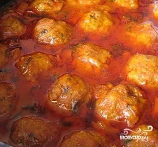 Достать из холодильника тефтели, положить их в кипящий соус. Аккуратно покрыть тефтели соусом, закрыть крышкой, дать протушиться 20 минут.