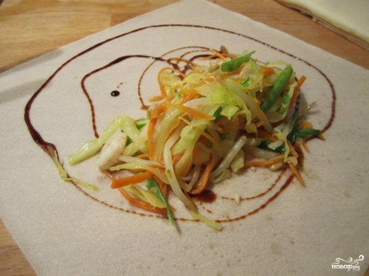 Рисовую бумагу выложите на стол и смочите водой с помощью кисточки, чтобы она не поламалась. По желанию добавьте соевый соус. Потом выложите начинку.