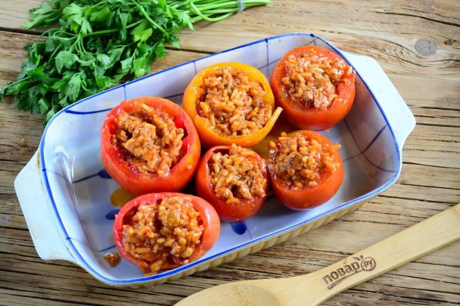 Смешайте подготовленную мясную начинку с мелко порубленной зеленью (укропом, петрушкой, мятой). Полученной смесью нафаршируйте помидоры. Помидоры поставьте в форму для запекания, накройте шляпками, которые мы срезали в начале. В форму налейте 3 ст. ложки воды и отправьте в духовку на 35 минут (температура - 180 градусов).