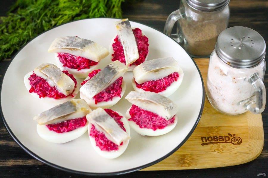 Выложите на массу ломтики сельди, стряхнув их от масла. Можно приобрести малосольное филе сельди, удалите косточки и нарезать его ломтиками, если вы не любите еду из пресерв.