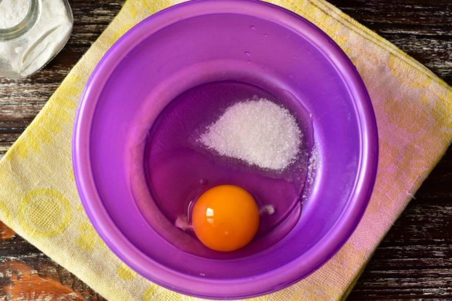 В миску вбейте куриное яйцо, добавьте соль и сахар.