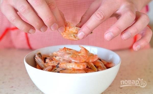 1. В кастрюлю влейте воду или бульон и доведите до кипения. Креветки ошпарьте кипятком, немного остудите и очистите.