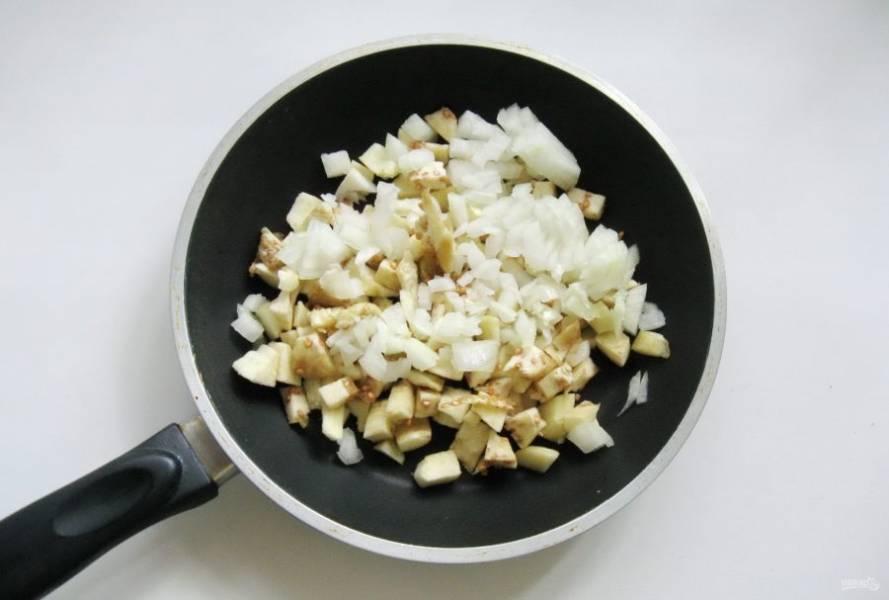 Добавьте мелко нарезанный репчатый лук. Налейте подсолнечное масло и обжаривайте баклажаны с луком в течение 10 минут, помешивая.