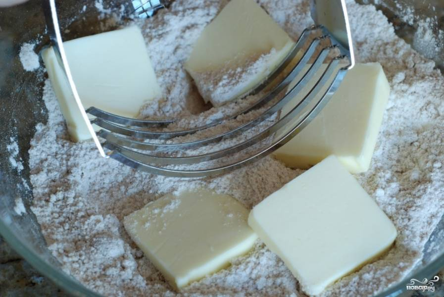 Тем временем в отдельную миску просеиваем оставшуюся муку, добавляем оставшийся сахар, коричневый сахар и корицу. Перемешиваем, добавляем кубики сливочного масла.