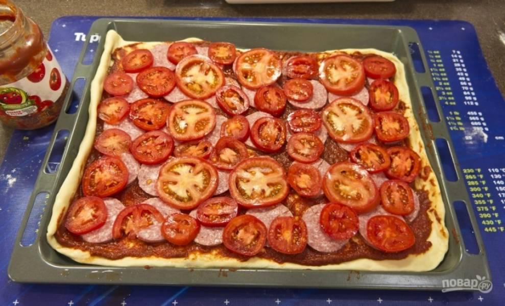 Смазываем тесто томатной пастой по всей площади и выкладываем начинку: порезанную произвольными кусочками колбасу и/или ветчину, помидоры кружочками, нарезанные оливки, присыпаем пиццу ароматным орегано.