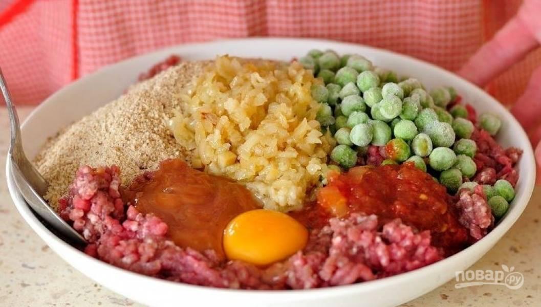 """В большой миске соедините говяжий фарш с зеленым горошком, панировочными сухарями, соусом """"Барбекю"""", томатным соусом. Вбейте сырое куриное яйцо, посолите и поперчите. Тщательно все перемешайте."""