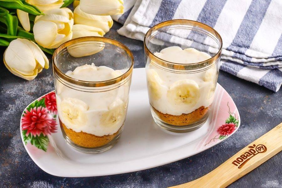 Второй банан очистите от кожуры, нарежьте ломтиками, разделите на две порции и одну из них выложите в крем, примыкая к стенкам стаканов или чашек, если они прозрачные.