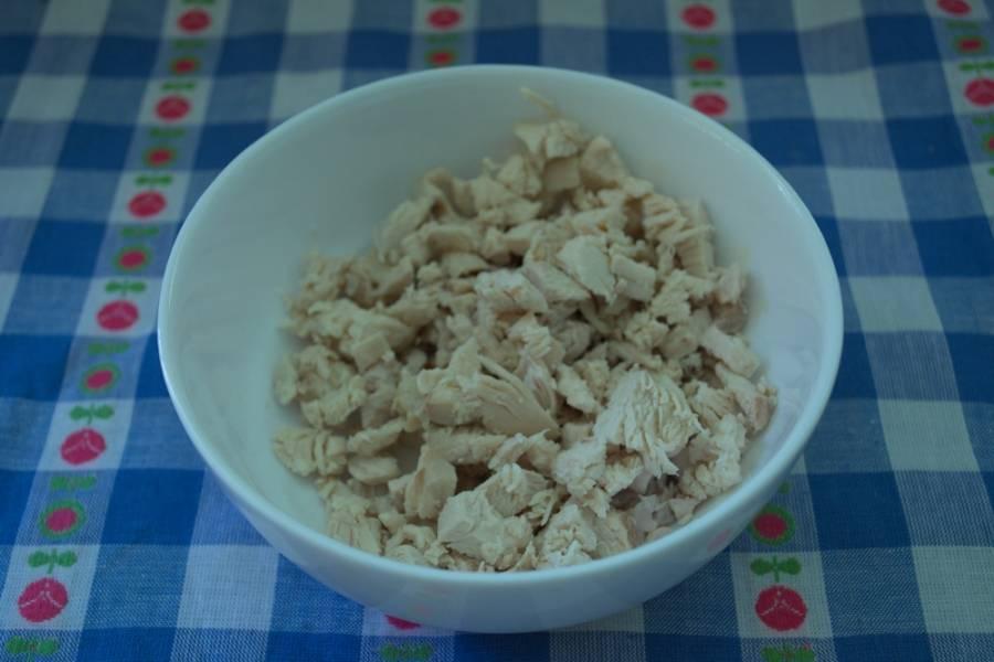 1. Отварите курицу. Снимите с кости, удалите кожу. Мясо нарезать мелко. Вкуснее салат будет, если взять мясо с ноги птицы.