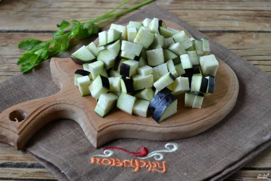 Баклажаны, не очищая от кожицы, порежьте средними кубиками. Пересыпьте солью, слегка помните и оставьте на 20 минут, чтобы вместе соком убрать горечь.