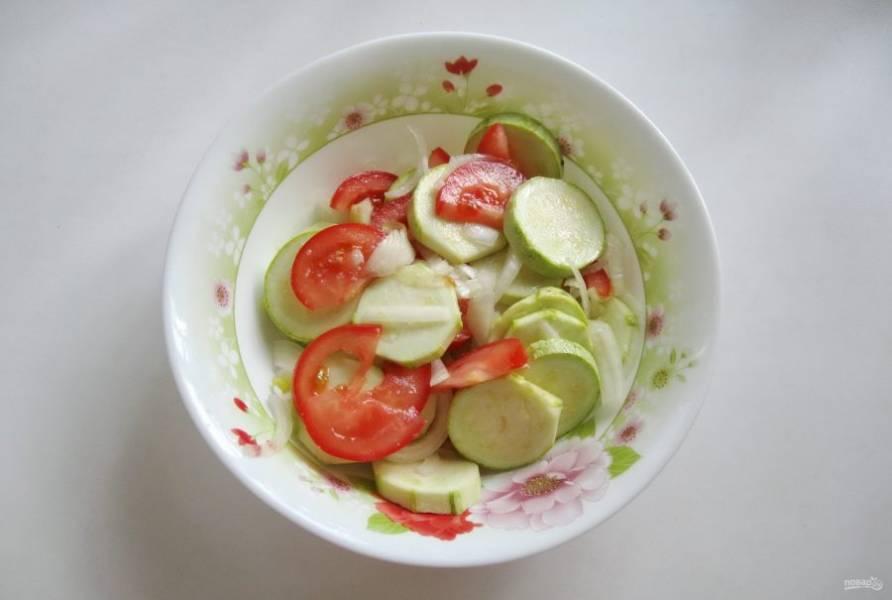Помидоры помойте и нарежьте дольками. Выложите в миску с кабачками и луком. Посолите овощи по вкусу и перемешайте.