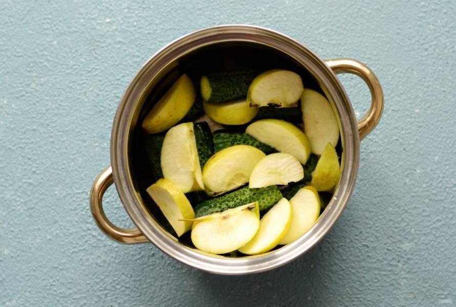 Яблоки нарежьте на четвертинки, не удаляя сердцевину. Переложите в кастрюлю к огурцам.