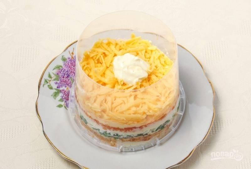 Также на терке натрите твердый сыр, выложите его в кулинарное кольцо. Смажьте сырный слой майонезом. Натрите на мелкой терке отварной желток и присыпьте им последний слой. Украсьте салат зеленью. Дайте ему настояться в холодильнике — и подавайте к столу.