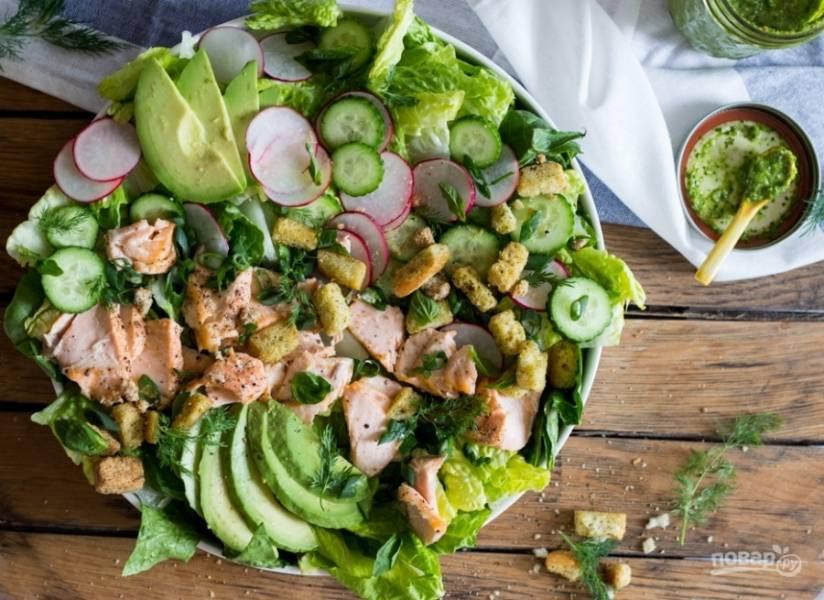 Укладываем на блюдо листья салата. Дальше красиво выкладываем измельченную зелень, авокадо, огурцы, редис и рыбу. Можно заправить салат оливковым маслом. Приятного аппетита!