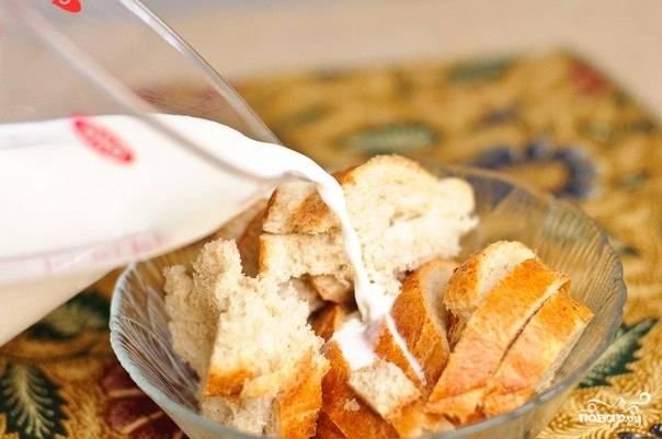 Раскрошите батон на мелкие кусочки и залейте свежим молоком. Дайте батону размокнуть. Разомните мякоть вилкой.