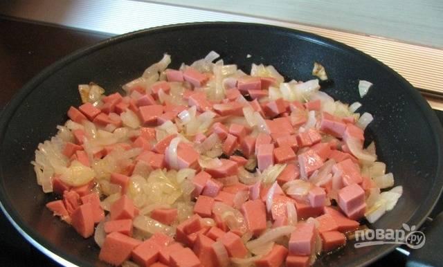 В масле обжарьте нашинкованный лук в течение 5 минут. Потом к нему добавьте нарезанную кубиком колбасу. Перемешайте и готовьте ещё 5 минут.