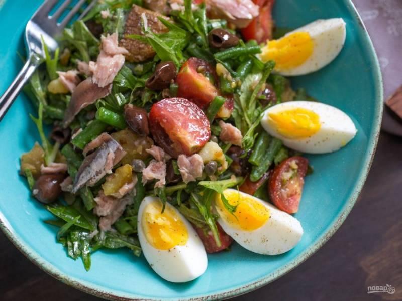 8.При подаче выкладываю салат на блюдо, добавляю измельченные на 4 дольки куриные яйца, украшаю анчоусами.
