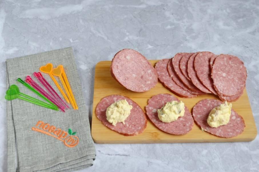 5. Колбаску порежьте тонко. Положите по ложечке начинки.