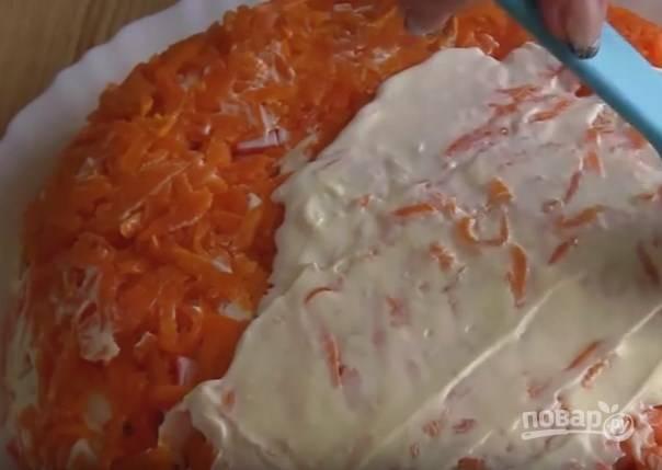 8. Лук покройте майонезом, выложите креветки, затем — яйца. Смажьте всё майонезом и очередным слоем положите крабовые палочки, затем майонез, морковь и снова майонез.