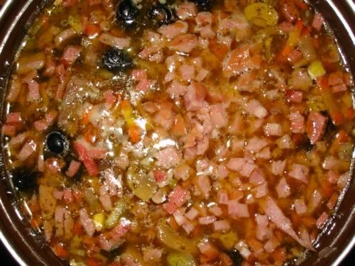 Кастрюлю ставим на огонь. В кастрюлю наливаем мясной бульон, в него добавляем зажарки и нарезанные тонкой соломкой соленые огурцы, оливки или маслины. Можно добавить немного рассола. На медленном огне немного варим, затем отключаем печь и даем настояться солянке около часа.