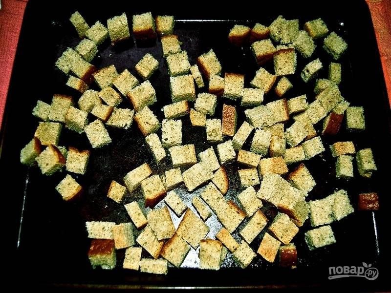 Тем временем приготовьте сухарики: сливочное масло растопите в микроволновке или на слабом огне на сковороде, добавьте измельченный чеснок, перемешайте и залейте этим маслом нарезанный на квадратики хлеб. Посолите крупной солью, посыпьте острым перцем (по желанию), хорошо перемешайте и запекайте сухарики в духовке 7-10 минут при температуре 160 градусов.