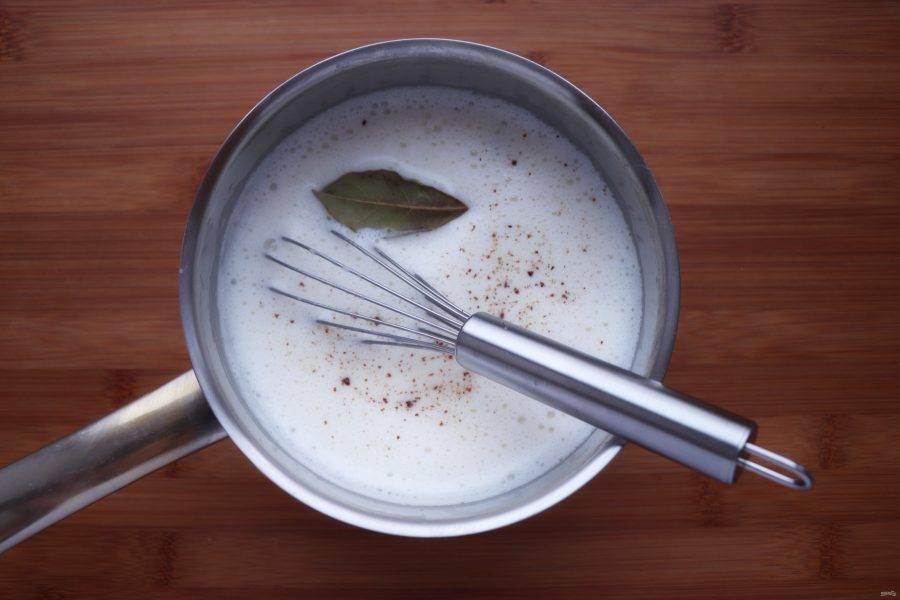 Приготовьте соус для заливки мусахи. Для этого в сотейнике распустите сливочное масло и обжарьте на нем 1 столовую ложку муки. Затем потихоньку влейте подогретое молоко, непрерывно помешивая венчиком. Когда все молоко будет влито, добавьте соль, лавровый лист и немного мускатного ореха. Тем временем взбейте в миске 1 яйцо и влейте к нему небольшое количество горячего соуса, также помешивая. Эту смесь перелейте обратно в сотейник с соусом и варите до загустения 1-2 минуты. Готовый соус снимите с огня и поместите в емкость с холодной водой.