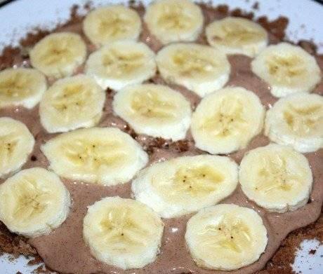 Кружки пряников выложить на блюдо, промежутки засыпать пряничной крошкой. Залить сверху кремом и уложить слой бананов.